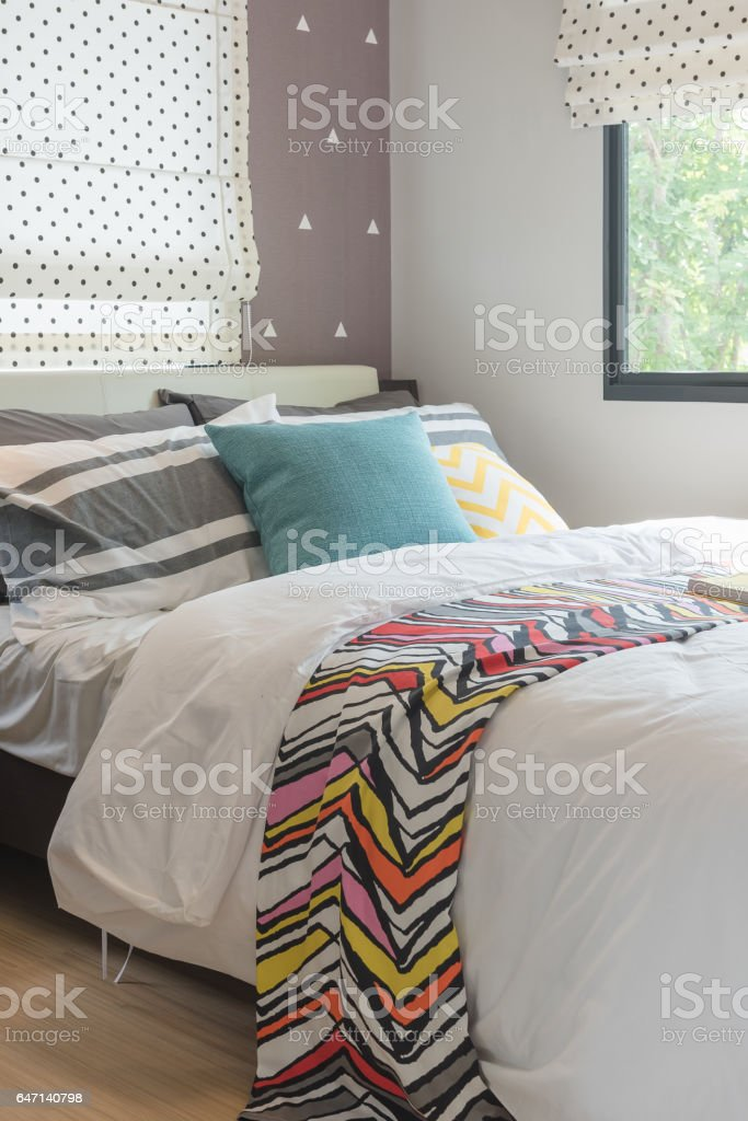 colorful pillows set on bed in modern bedroom stock photo