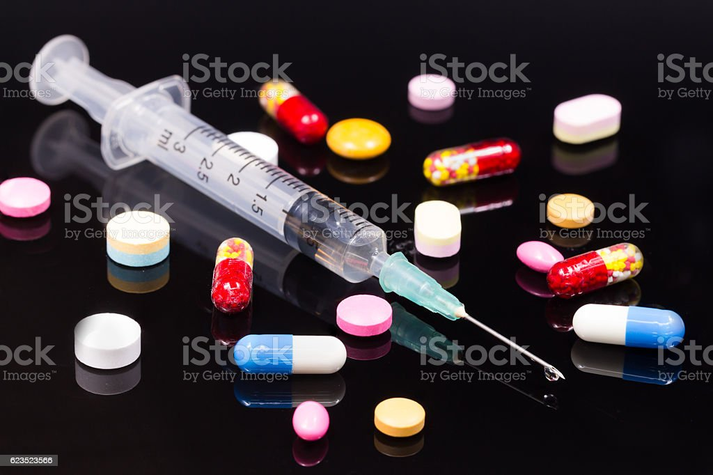 Colorful pills and syringe over dark background stock photo