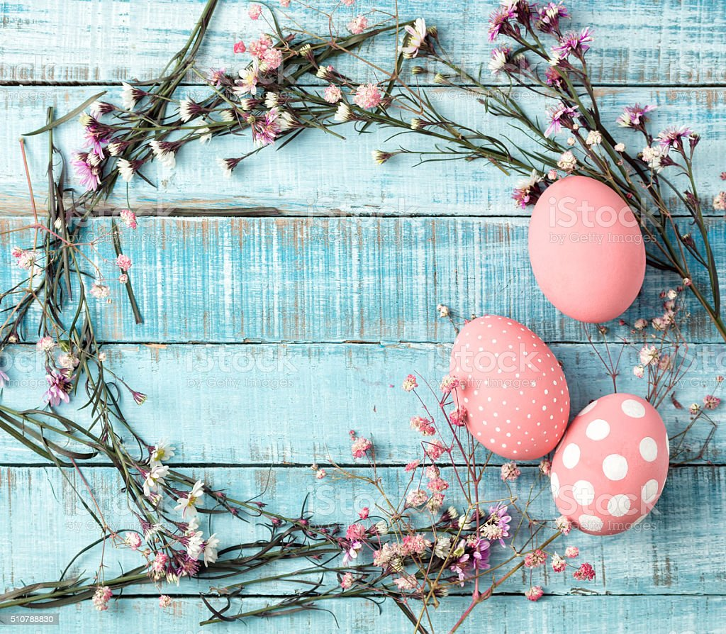 colorful pink eggs and flower frame on blue wood stock photo