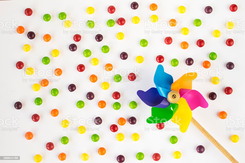 Colorful pinwheel and candies on white background. Top view. Flat stock photo