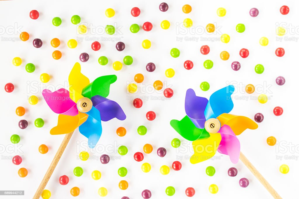 Colorful pinwheels and candies on white background. Top view. Flat stock photo