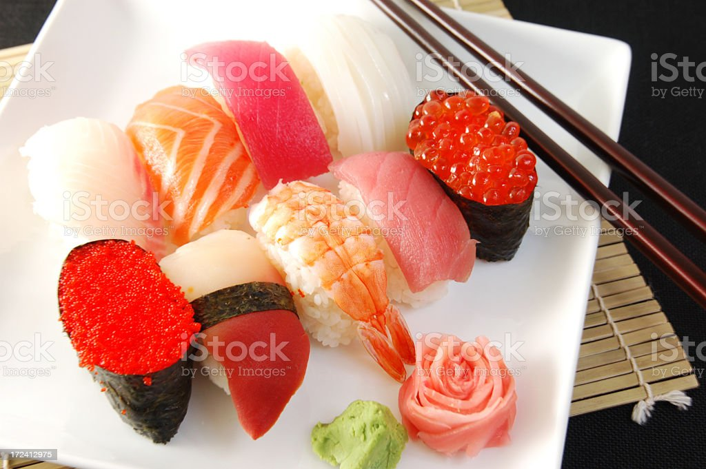 Colorful plate of sushi with chopsticks and bamboo mat royalty-free stock photo