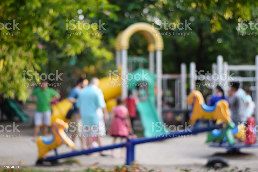 Colorful playground with children and parents in park (blur background) stock photo