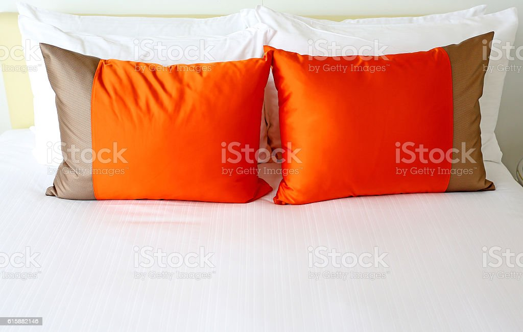 Colorful polka pillow on white bed stock photo