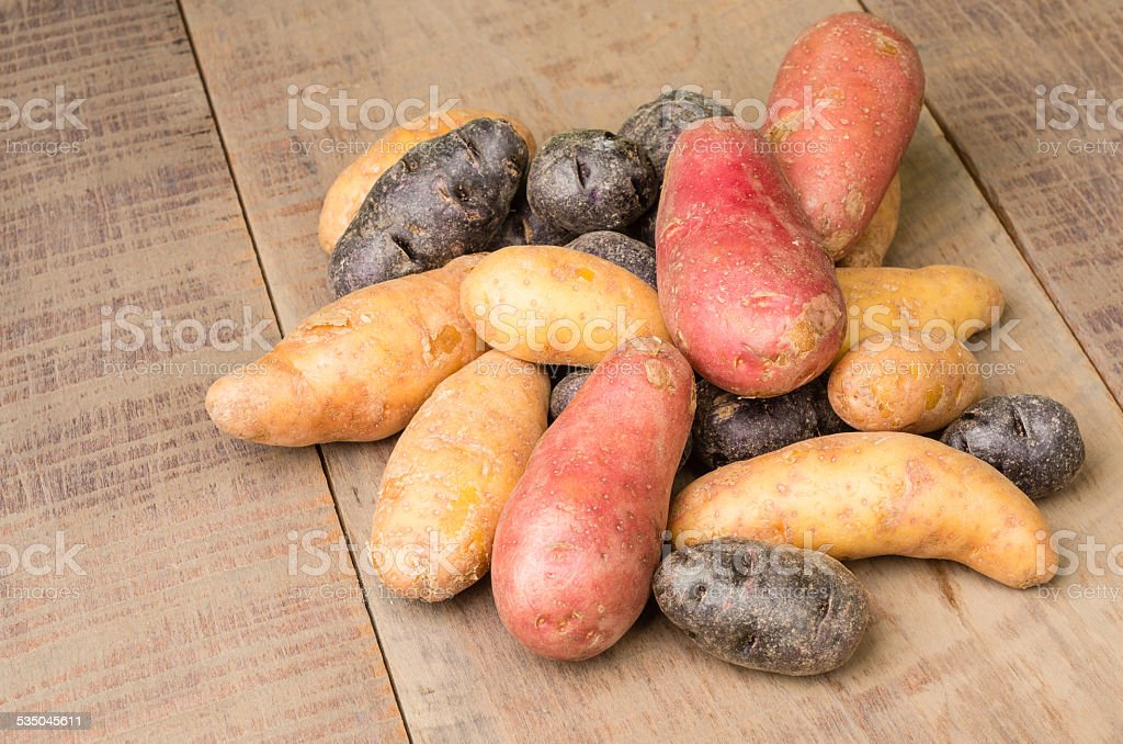 Colorful potatoes on table stock photo