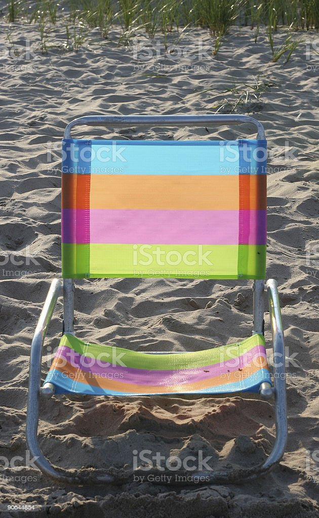 Colorful rainbow chair on sandy beach in the sunlight stock photo