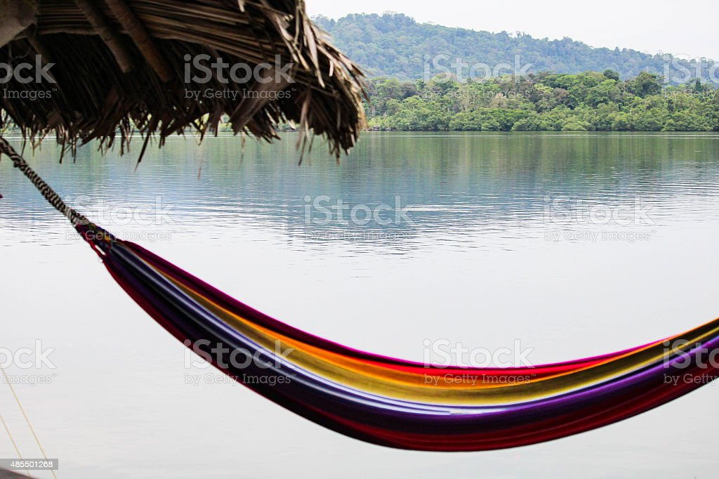 Colorful rainbow striped hammock overlooking the sea stock photo