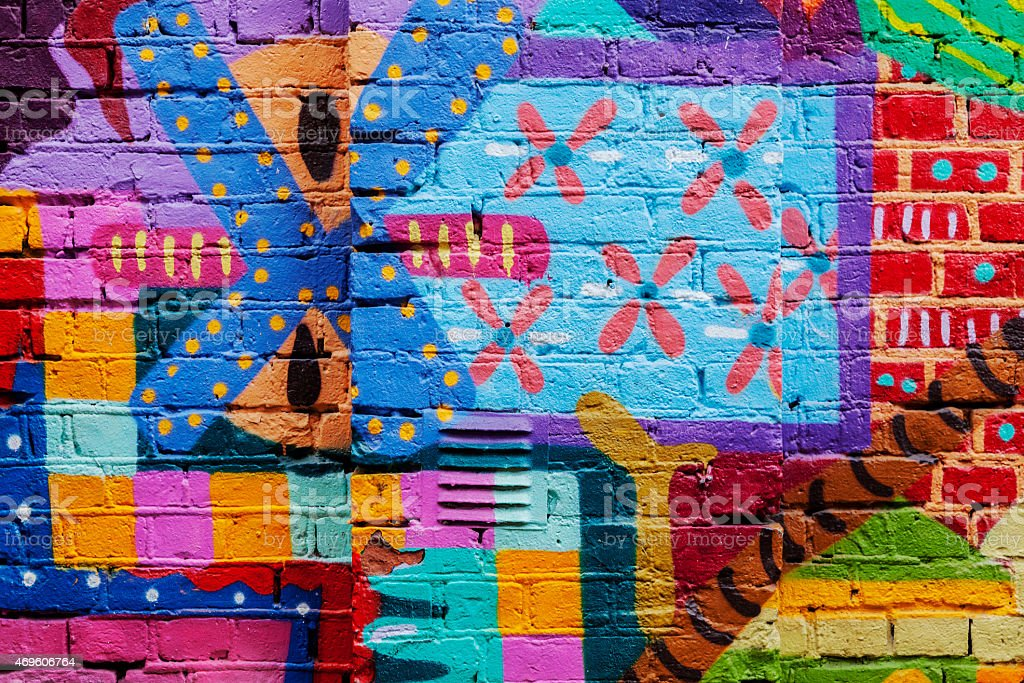 Colorful red yellow and blue graffiti on a brick wall. stock photo