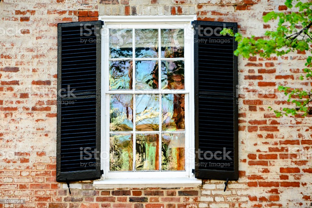 Colorful reflections in a window of an old brick building. stock photo