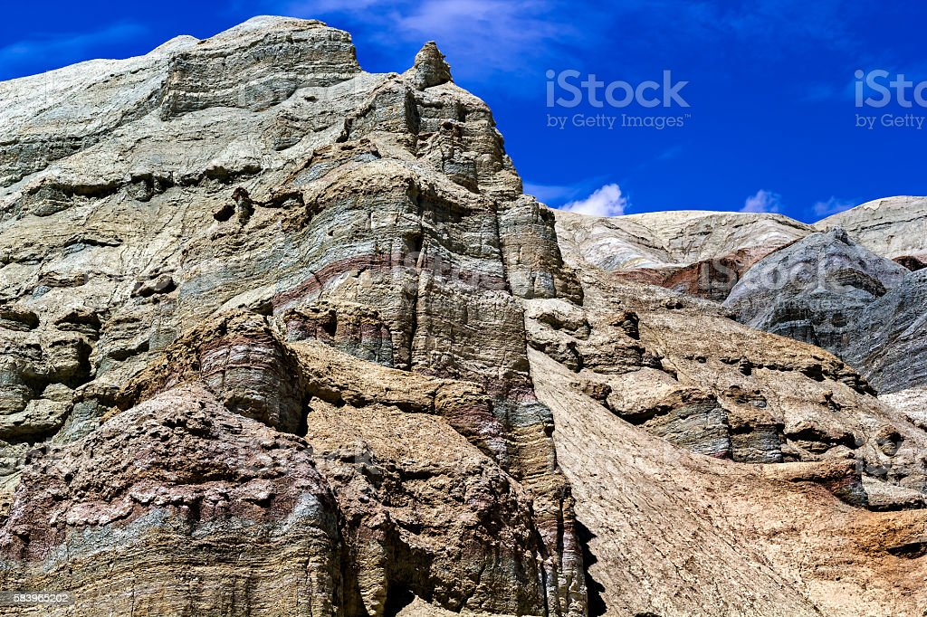 colorful rocks on the background of blue sky with clouds stock photo