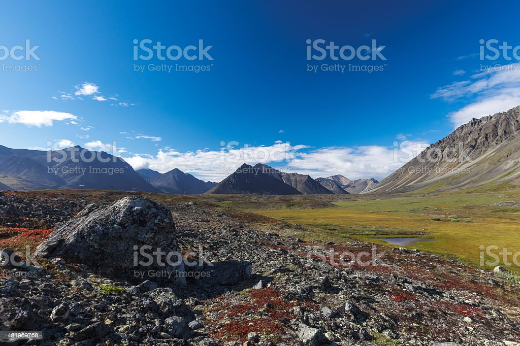 Colorful rocky tundra in front of river valley between mountain stock photo