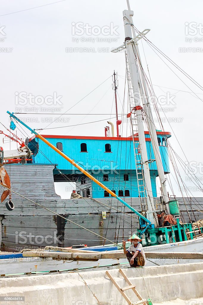 Colorful rusty ship in Jakarta harbor with fishermen on board stock photo