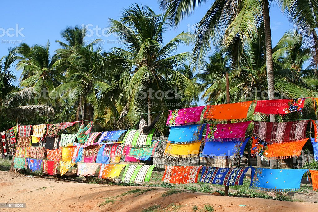 Colorful Sarongs at informal market hanging below coconut palm trees stock photo