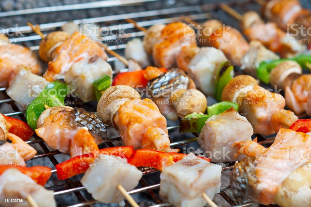 Colorful seafood skewers on the grill royalty-free stock photo