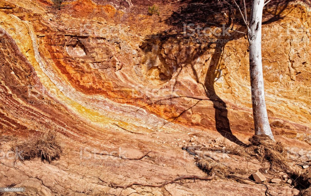 Colorful sedimentary rock formations at Glen Helen Gorge water hole stock photo