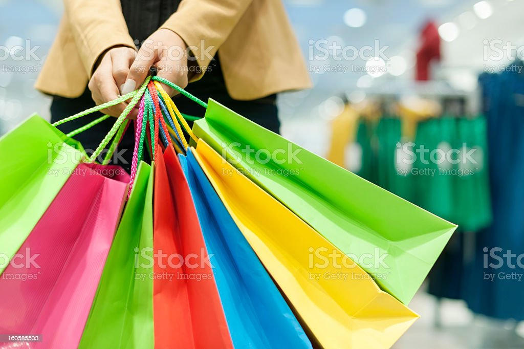 Colorful shopping bags being held on blurry mall background stock photo