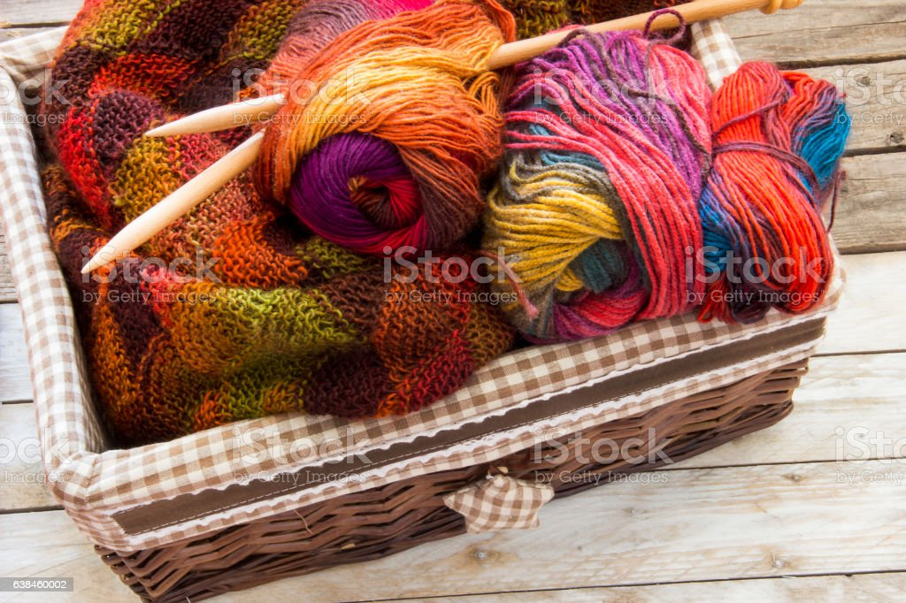 Colorful skeins of wool and wood needles in knitting basket stock photo