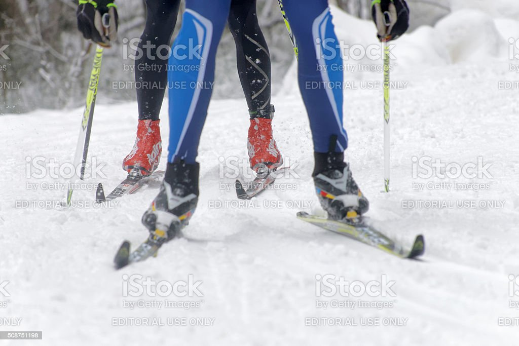 Colorful skies, feet and legs of two cross country skiers stock photo