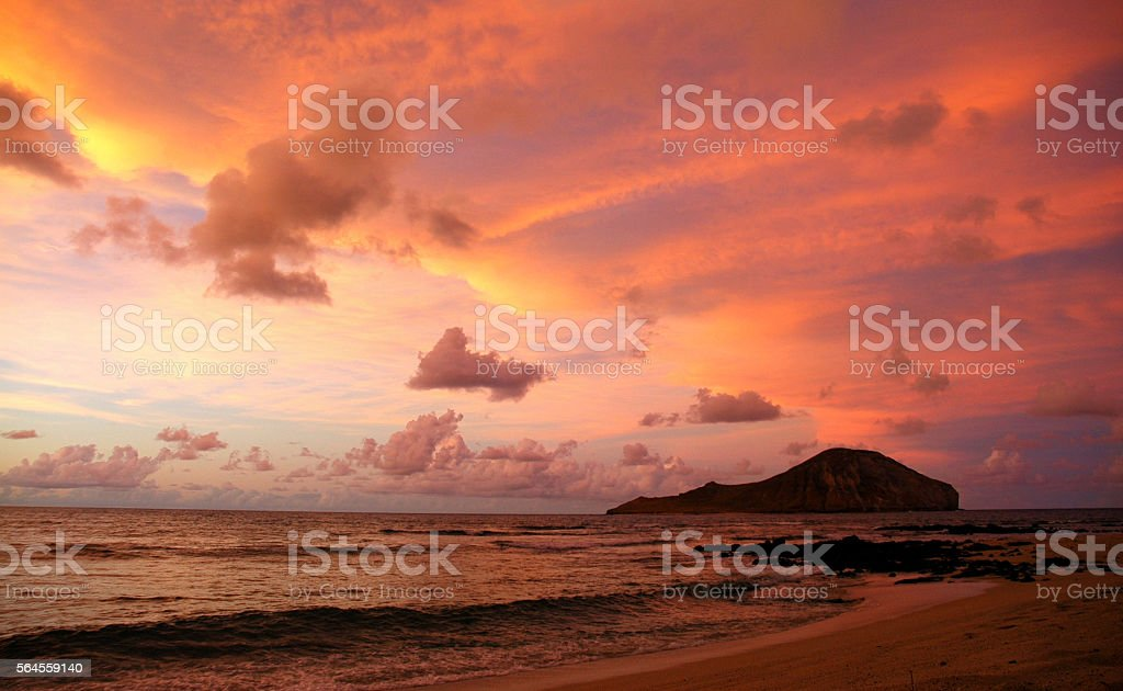 Colorful sky reflected in waves on sandy beach and island stock photo