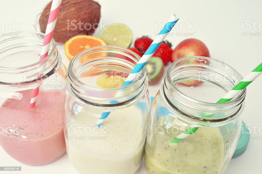 Colorful smoothie in modern jars with straws stock photo