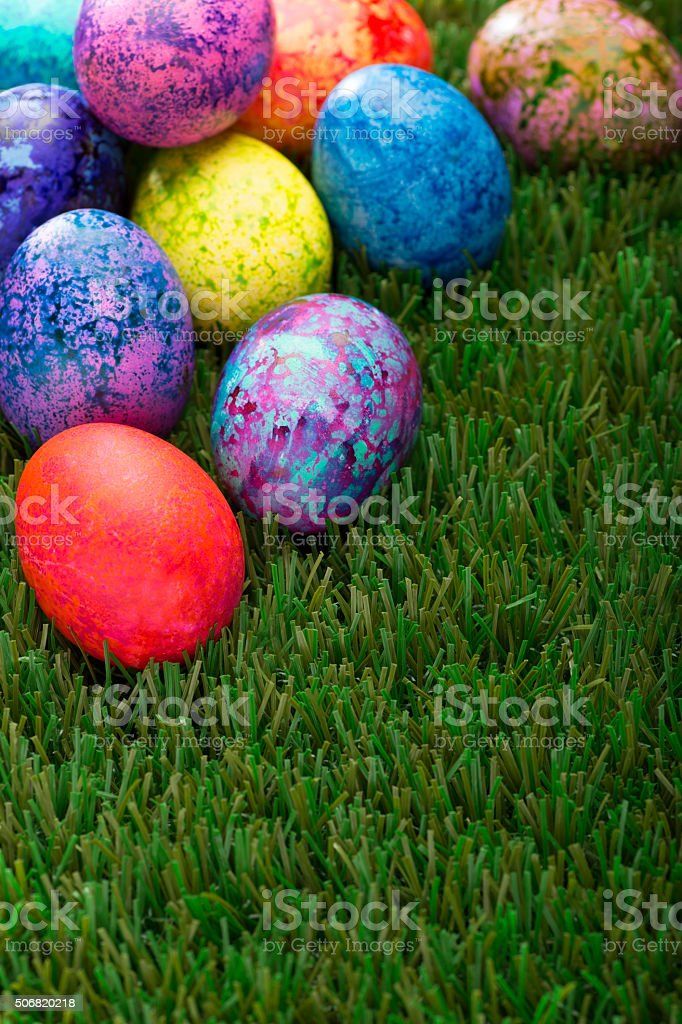 Colorful Speckled Easter Eggs on Green Grass stock photo