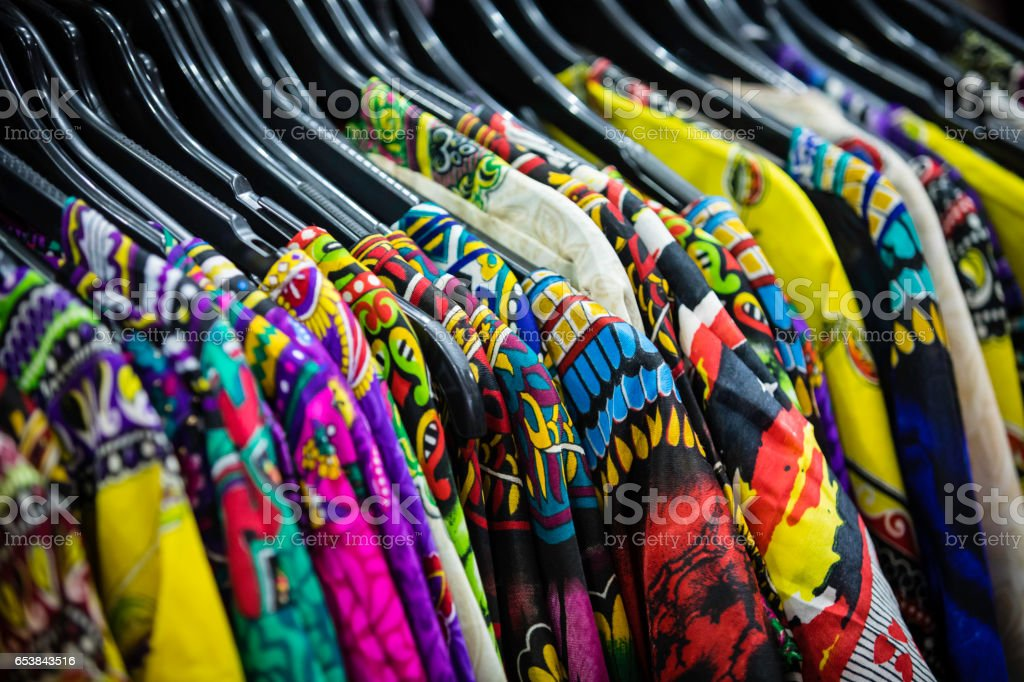 colorful Sri Lankan dresses and shirts hanging on hangers stock photo