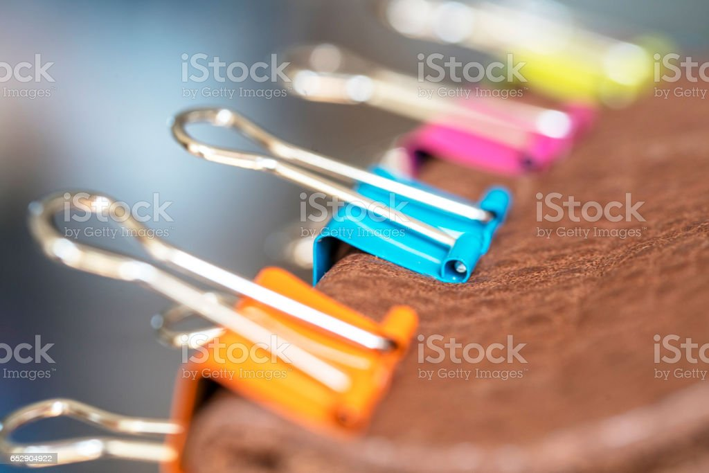 colorful stationery clips on leather stock photo