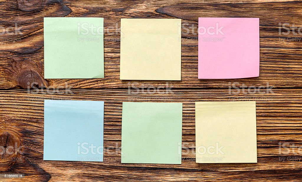 Colorful stickers on the wooden wall stock photo