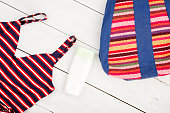 colorful striped bag, swimsuit, sunscreen