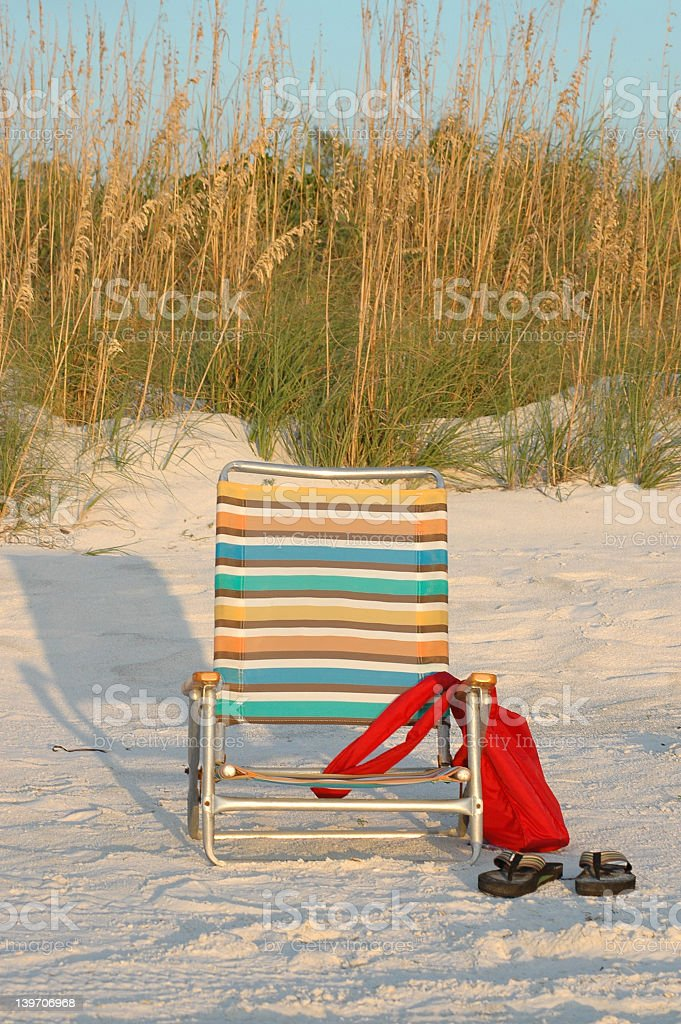 Colorful striped beach chair with red tote and flip flops stock photo