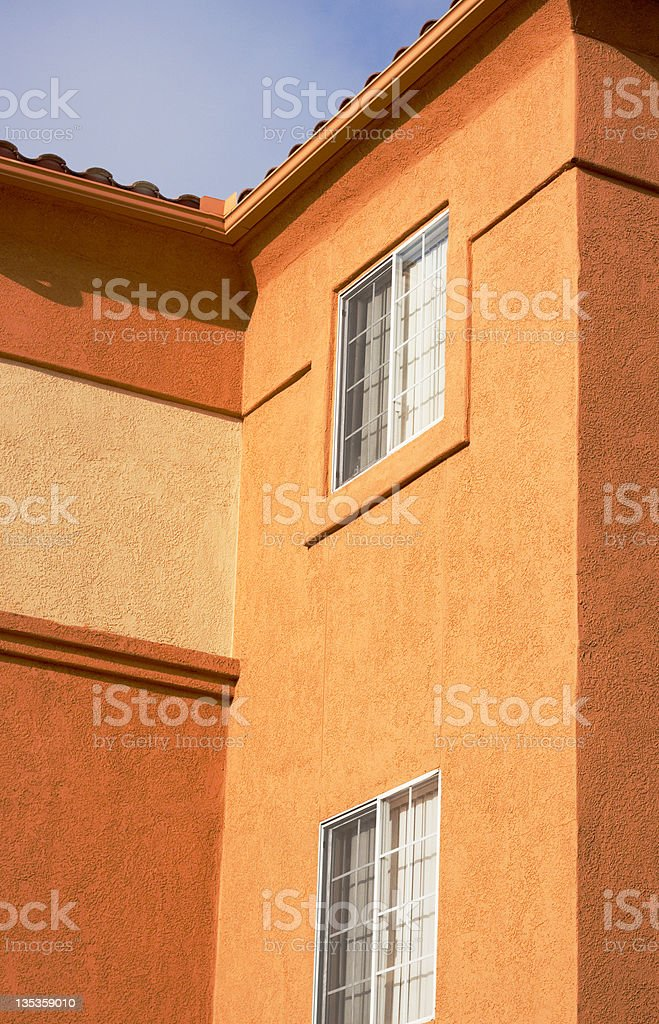 Colorful Stucco Apartment Building Exterior and Blue Sky royalty-free stock photo