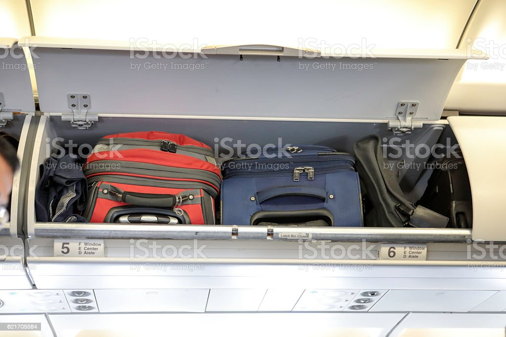 Colorful suitcases in overhead bin on airplane stock photo