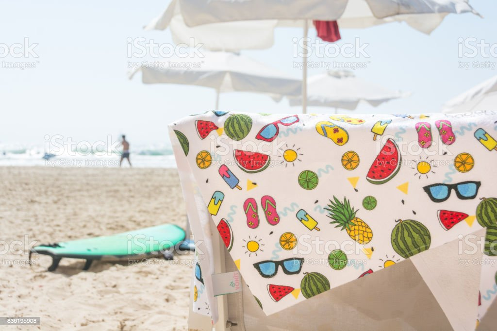 Colorful summer beach towel on chair stock photo