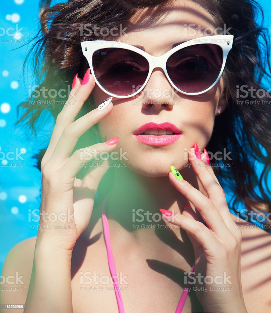 Colorful summer portrait of young attractive brunette woman wearing sunglasses stock photo