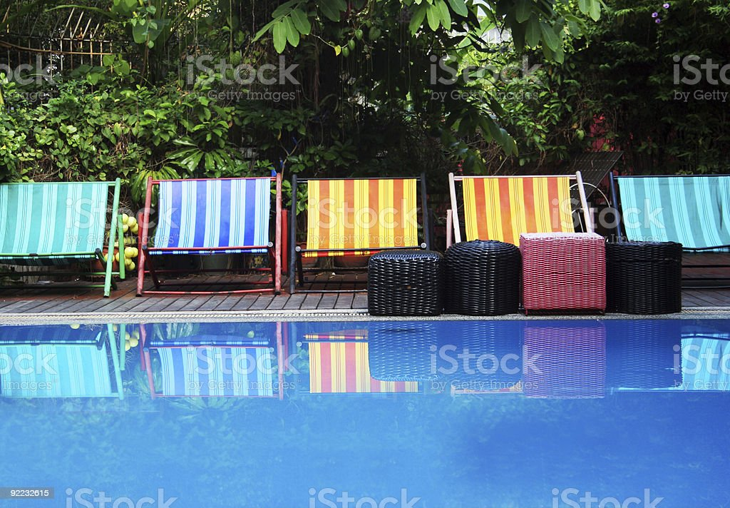 Colorful sun loungers by a clear swimming pool stock photo