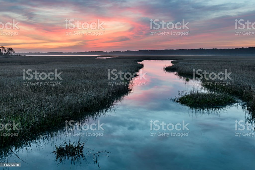 Colorful Sunrise Over Inlet with Water Reflections stock photo