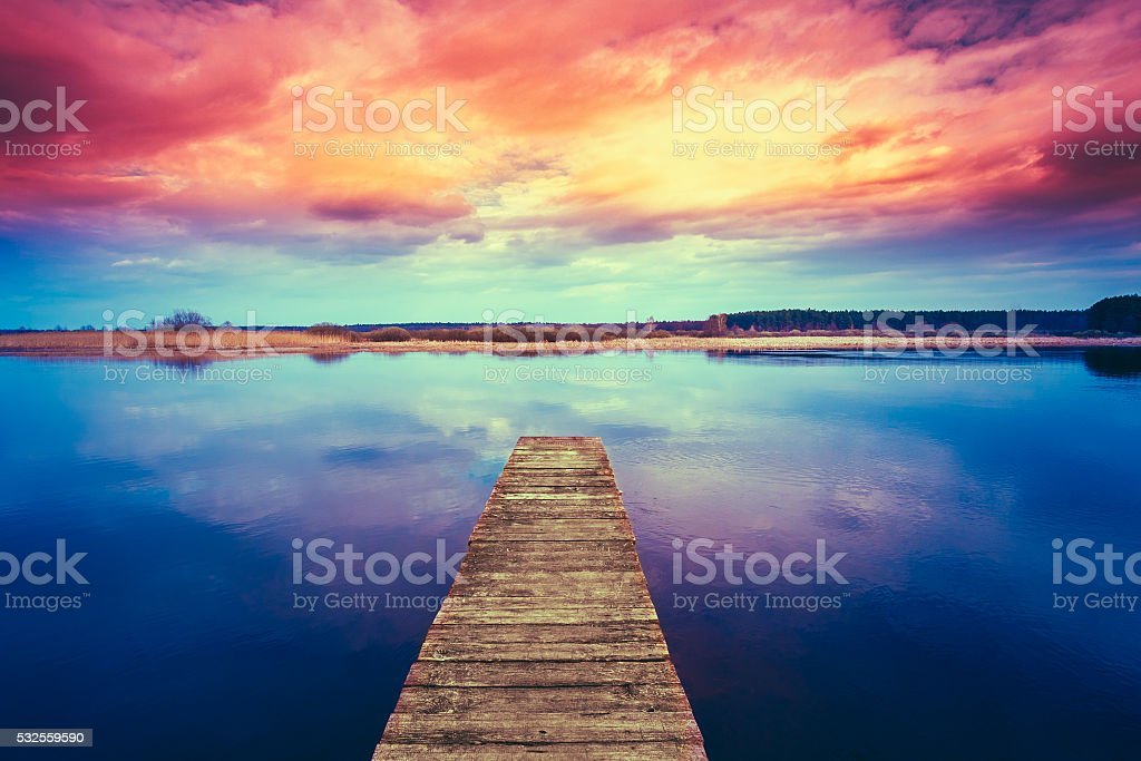 Colorful sunset dramatic sky over wooden boards pier  Calm Water stock photo