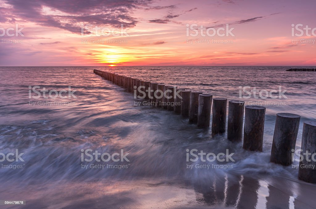 Colorful sunset on Baltic sea beach with wooden groyne stock photo