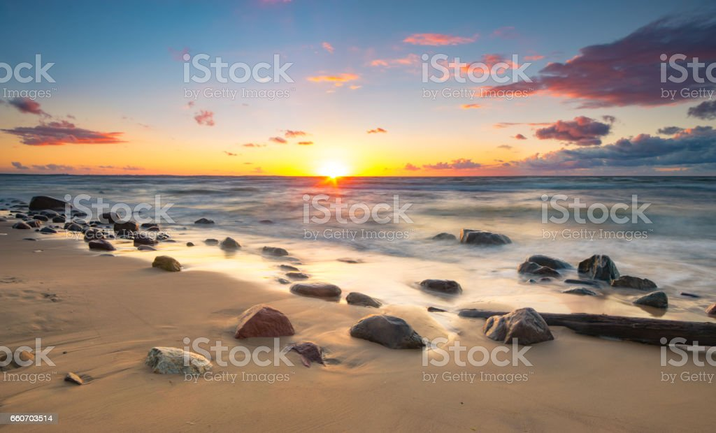 Colorful sunset over a sea beach during a storm stock photo