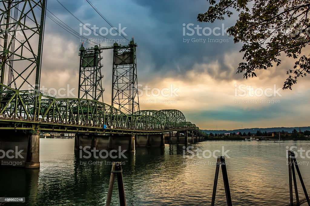 Colorful Sunset Over Columbia River Oregon Washington Bridge Dense Clouds stock photo