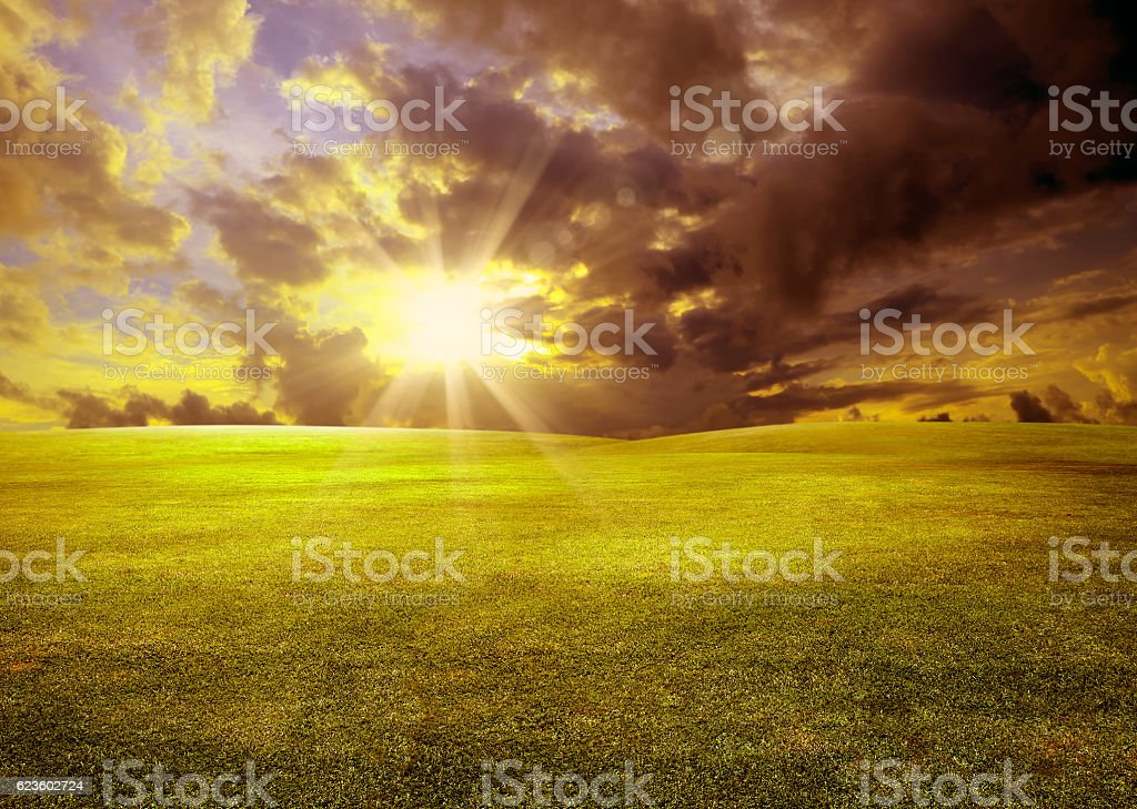 colorful sunset over green landscape stock photo