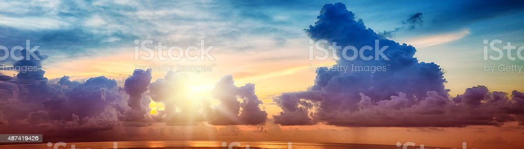 Colorful sunset over pacific ocean with stormy sky panorama stock photo