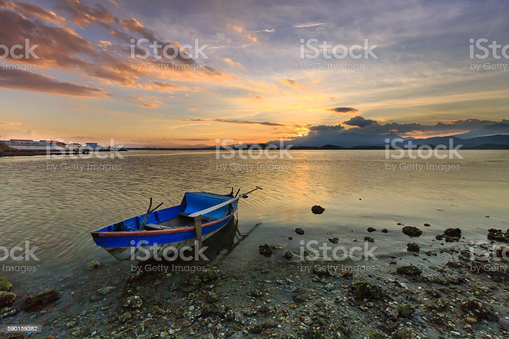 Colorful sunset over the lake with a old wooden boat stock photo