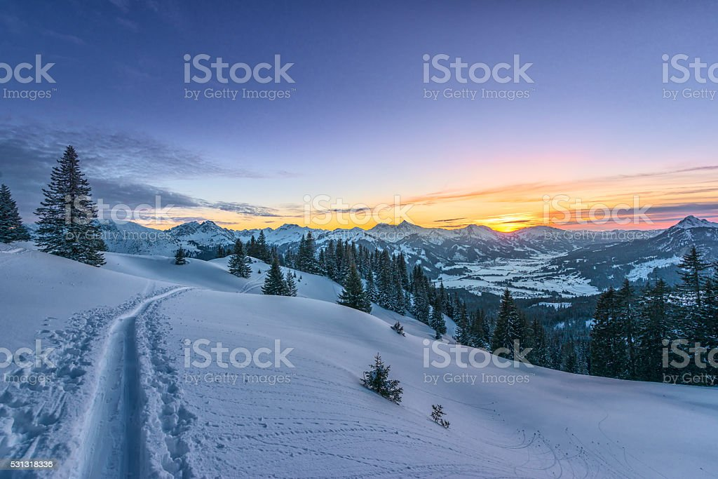 colorful sunset view from ski track on snowy field stock photo
