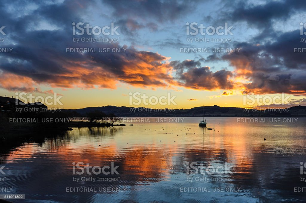 Colorful sunset with a boat  in Lake Taupo, New Zealand stock photo