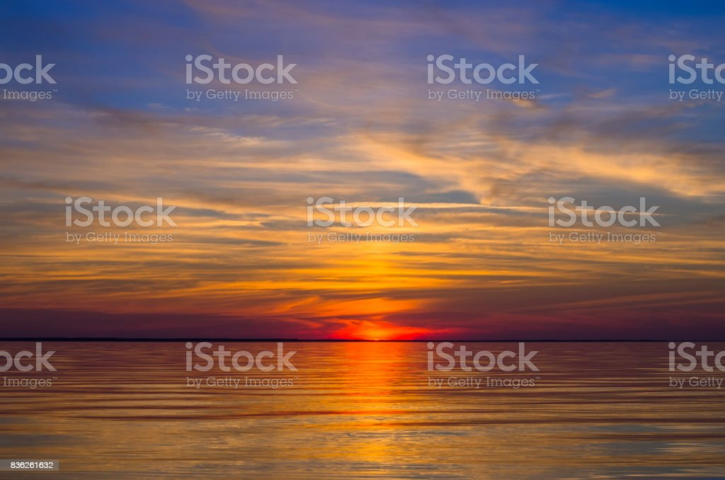 Colorful sunset with blue cloudy sky above sea. Relaxation landscape stock photo