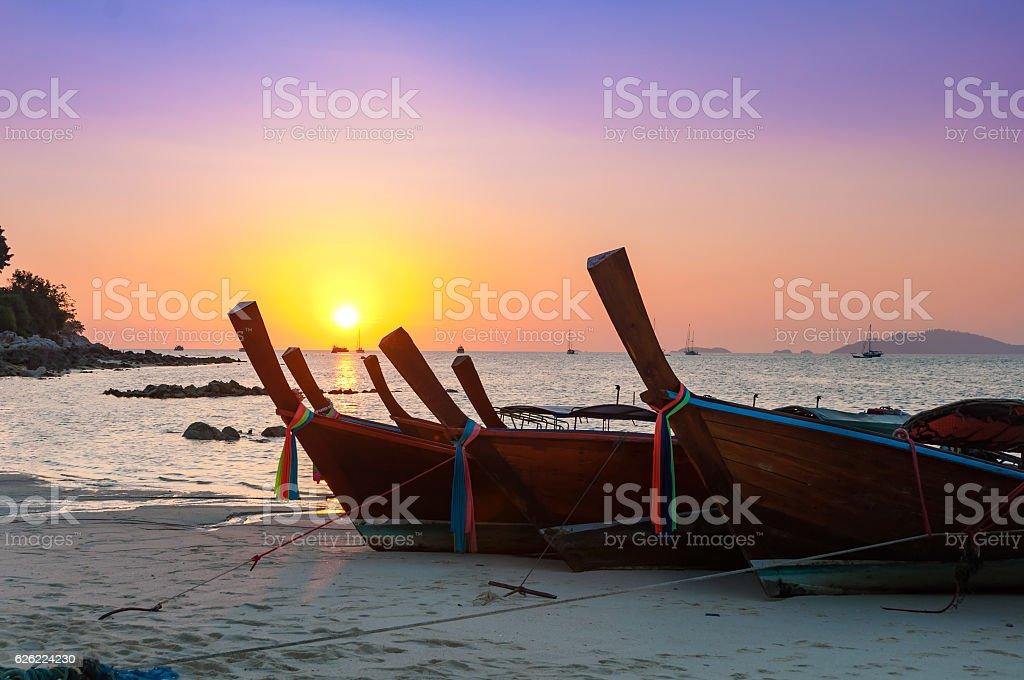 Colorful sunset with Thai traditional longtail boat on the beach stock photo