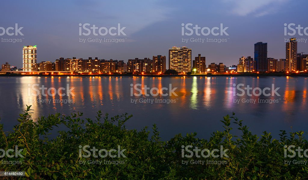 Colorful Taipei city lights reflecting in Tamsui River at night stock photo