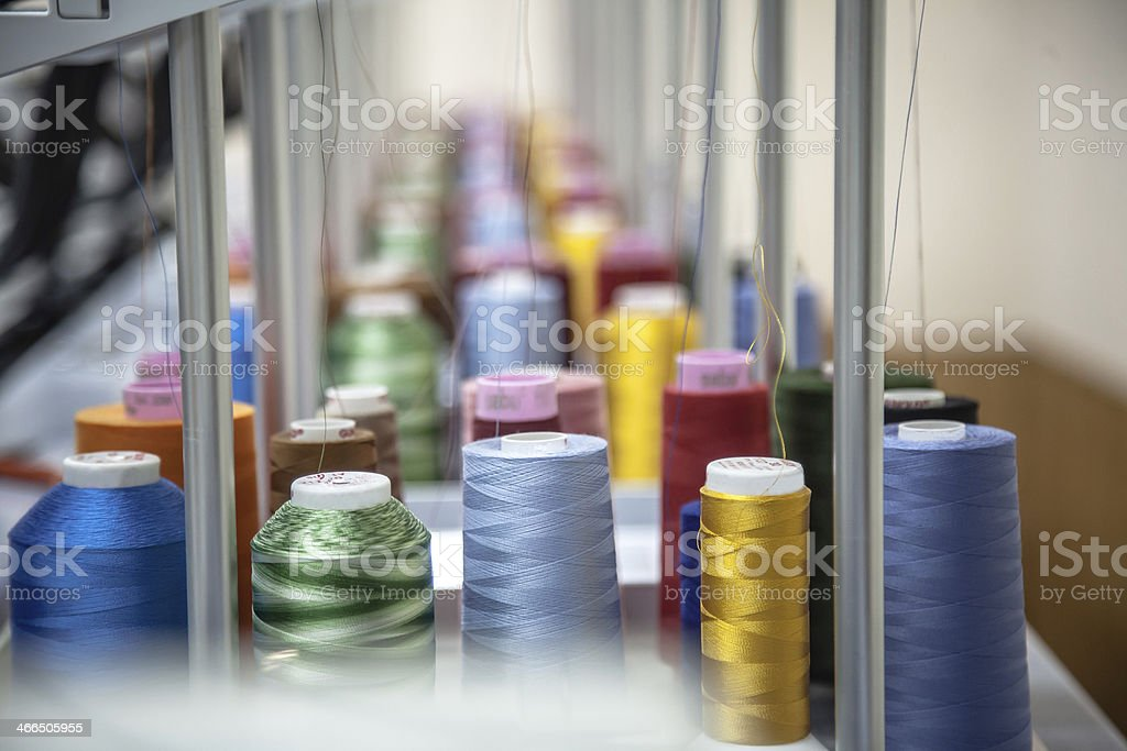 Colorful thread reels sitting in an orderly fashion stock photo
