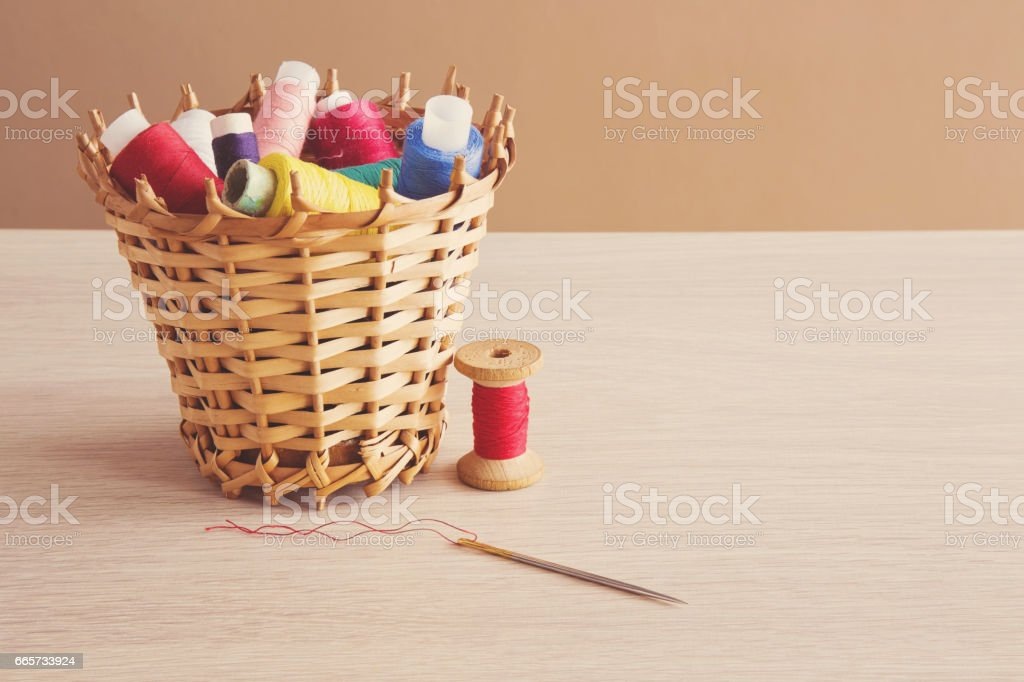 Colorful threads in the basket with red thread spool and needle on the wooden table. Sewing works. Handmade. stock photo